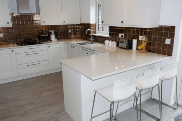 White gloss shaker style kitchen with tiled splashback quartz worktop